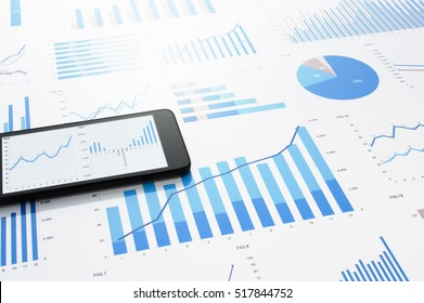 Many charts and graphs. Concept image of data gathering. Accounting data and smartphone on gray reflection background.