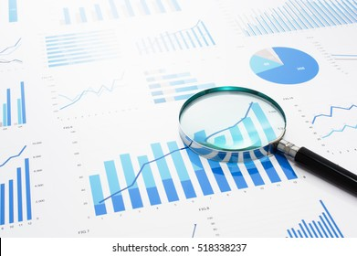 Many charts and magnifying glass. Reviewing data. Financial reports and magnifying glass. Reflection background.