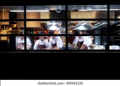 many chefs busy in kitchen