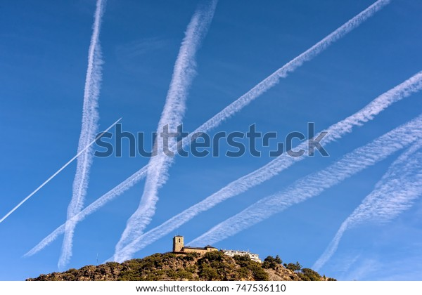 Many chemtrails on blue sky over catholic church in Spain.