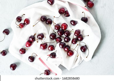 many cherry berries are scattered on a white kitchen towel on a gray background