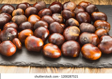 many chestnut fruits are located on a wooden table view from the side