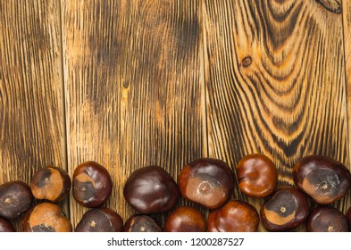 many chestnut fruits are located on a wooden table top view. top copy space