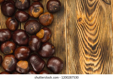 many chestnut fruits are located on a wooden table top view right copy space