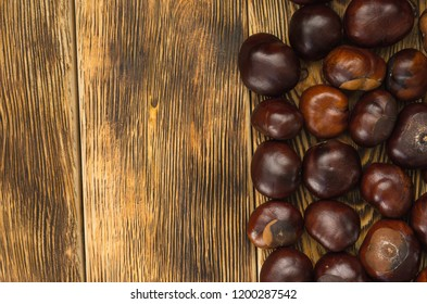 many chestnut fruits are located on a wooden table top view left copy space