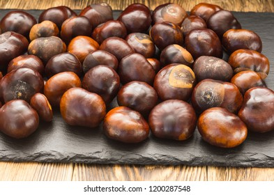 many chestnut fruits are located on a dish of natural slate lying on a wooden table, a side view