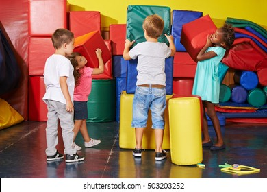 Many children helping together to tidy up in a preschool gym