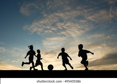 Many children were playing soccer at sunset.
