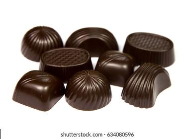 Many chokolate candies isolated on white background, close-up