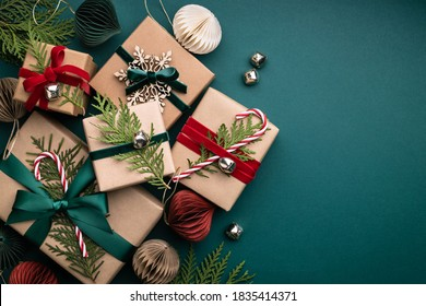 Many Christmas gift boxes tied velvet ribbons with paper decorations on turquoise background. Holiday background in earth colours.