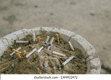 Many cigarette stub in sand ashtray. The rest of cigarettes in the ashtray. There are many types of cigarette stub on the sand in the ashtray. A cigarette is not good for health.