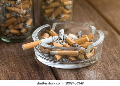 Many cigarette stubs and ash in a glass ashtray with bottle of cigarette stubs on wooden table