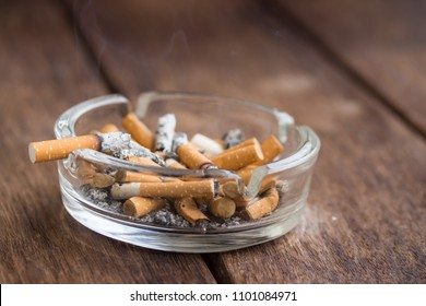Many cigarette stubs and ash in a glass ashtray on wooden table