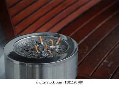 many cigarette stubs in the ashtyay near red bench at smoking area