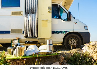 Many clean dishes outdoor on dish drying mat against camper vehicle. Washing up on fresh air. Camping on nature, dishwashing outside. Longing for an rv dishwasher.