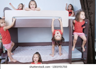 Many clone little girls on bunk bed in child room in domestic life. identical child crowd. Child omnipresent and playing everywhere