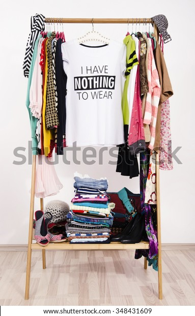 Many clothes on the rack with a t-shirt saying nothing to wear. Close up on a cluttered wardrobe with colorful clothes and accessories, many clothes and nothing to wear.