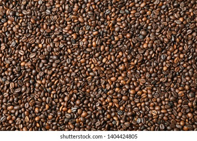 Many coffee beans as background, top view and space for text