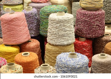 many coils and spools of fine colored wool thread for the creation of handmade sweaters