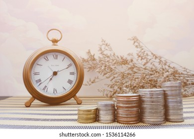 Many coins are stacked like stairs with a golden clock. Time concept. To remind that it's time to save the money, investment, expense for family or business in the future