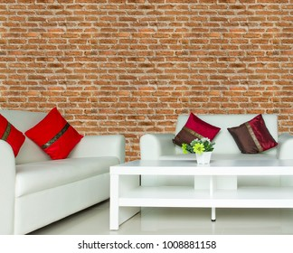 many color cushions on white sofa set in living room with brown brick wall