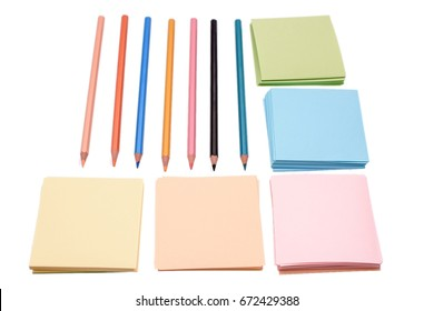 Many colored crowns and colored paper for writing, isolated on white background.