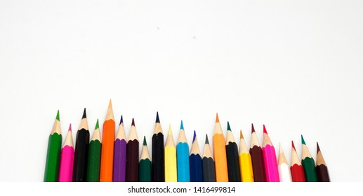 Many colored pencils on the white background of the child have space.