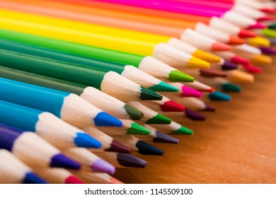 Many colored pencils on a wooden table. Back to school. Creation. Stationery. Art. Education.