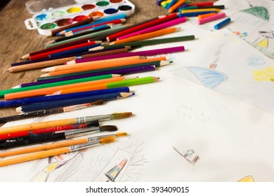 Many colored pencils and paint brush