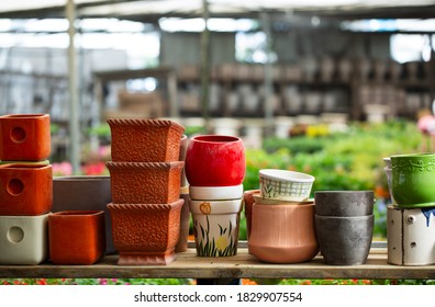 Many colored pots pots in a gardening store. Decorative plastic flowerpots. Recycling plastic. Production of plastic utensils for gardening