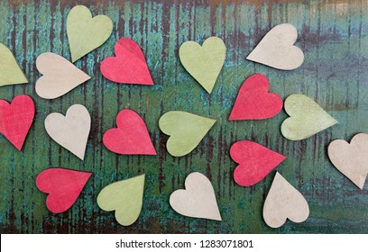 Many colored wooden hearts on an old colorful wooden plate