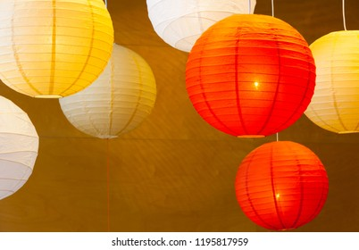 Many colorful balloon paper lamps against a wooden background