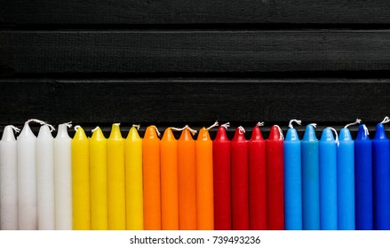 Many colorful candles in a single row and line, black background, candles of vibrant white. yellow, orange, red and blue colors, in a rainbow gradient