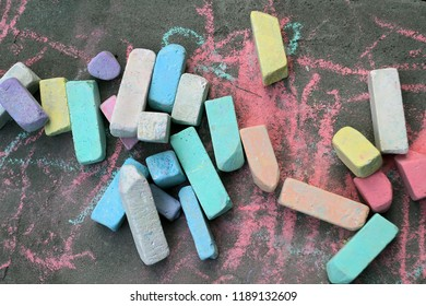 Many colorful chalks lie on the gray asphalt. Child creativity is not in the room, but in the street.