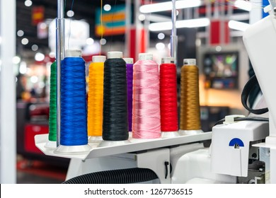 many colorful cotton reel thread set up at modern and automatic high technology sewing or embroidery machine for textile – clothing apparel making manufacturing process in industrial