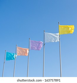many colorful flags waving over the blue sky background.