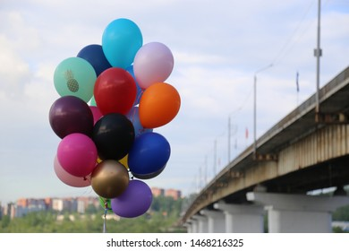 Many colorful helium balloons going up near the bridge