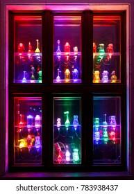 Many colorful illuminated bottles on window for decoration