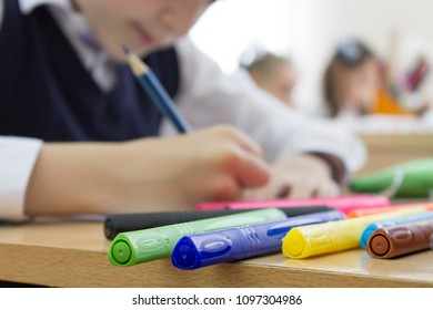 Many colorful markers on the table. A boy, a schoolkid in white shirt is drawing with a pensil in a notebook on background .
