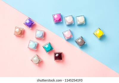 Many colorful nail polishes on pink and blue background. Flat lay. Top view. Fashion cosmetic set.