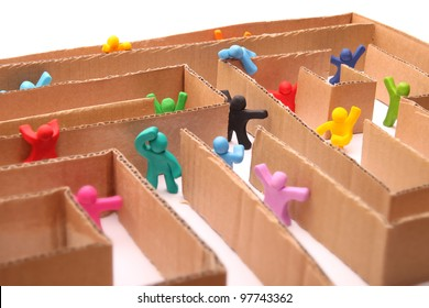 many colorful plasticine people running through paper maze