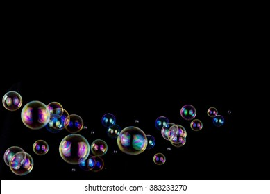 many colorful soap bubbles on black background with copy space