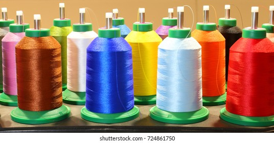 many colorful spools of thread in dressmaking factory and industrial decorations