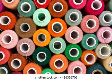 Many colorful spools of thread for sewing, colorful background