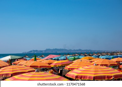 Many colorful sun umbrellas and parasols on a beach in Albania with horizon and city in the background.