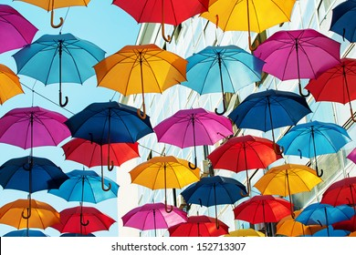 Many colorful umbrellas strung across the street.