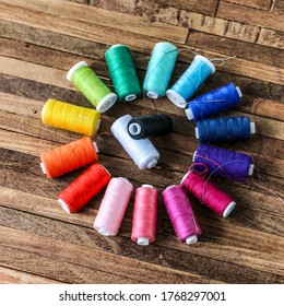many colorful wire spools on wooden table