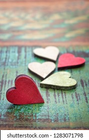 Many colorful wooden hearts on an old colorful wooden background