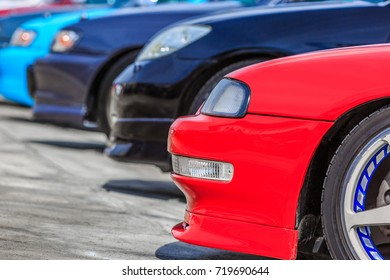 Many colourful cars parked in a row.