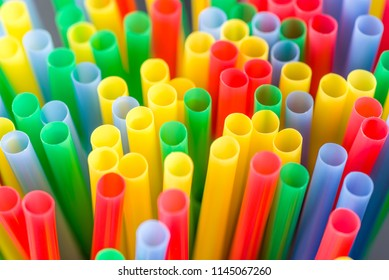 Many colourful plastic straws in a shallow depth of field and bright background